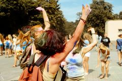 Happy hipster girls having fun with colorful powder at holi fest. Festival of colors in summer stock image