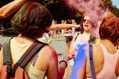 Happy hipster girls having fun with colorful powder at holi fest. Festival of colors in summer stock photo