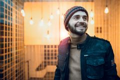 Happy hipster guy against the background of lamps. Royalty Free Stock Image