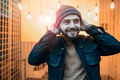 Happy hipster guy against the background of lamps. Holds his hands to the hat. Stock Photo