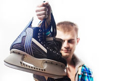 Happy hipster guy in a blue Aquamarine plaid  shirt is holding a ice skates on a white background isolated, lifestyle, winter spor. Happy hipster guy in a blue Royalty Free Stock Photos