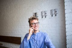 Happy hipster guy in casual wear having cellphone conversation during rest time in cafe. Smiling young businessman in stylish glasses talking on mobile phone Stock Photography