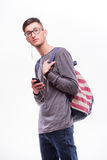 Happy hipster guy in glasses with backpack using a smart phone to listen music Stock Photo
