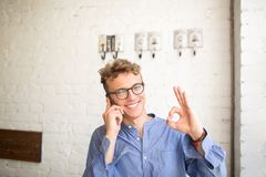 Young smiling businessman showing fingers okey while talking on mobile phone. Happy hipster guy having cell telephone conversation looking in camera while Stock Photos