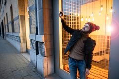 Happy hipster guy making selfie photo against the background of lamps. stock photo