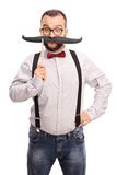 Happy hipster holding a fake mustache Stock Photo