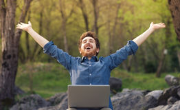 Happy hipster with laptop in the forest. Happy cheerful hipster man with a laptop sitting outdoors in nature, freedom and happiness concept Stock Images