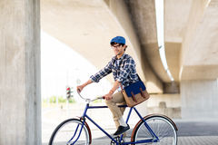 Happy hipster man with bag riding fixed gear bike Royalty Free Stock Image