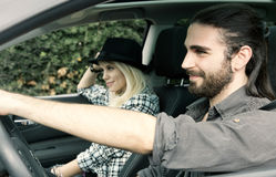 Happy hipster man with girlfriend driving car Royalty Free Stock Photo