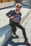 Happy hipster man holding hat in the street royalty free stock photo