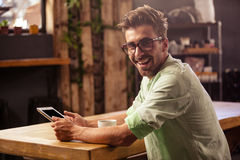 Happy hipster man posing for camera while using tablet Royalty Free Stock Photography