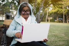 Happy hipster old women using computer in the park relax time on holiday Stock Image