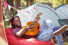 Happy hipster relaxing on campsite playing guitar Stock Photo