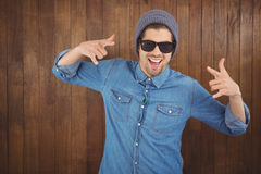 Happy hipster showing rock and roll hand sign Stock Image