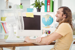 Happy hipster sitting by electric fan on computer desk Stock Photo