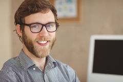 Happy hipster sitting at his desk Royalty Free Stock Images
