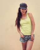 Happy hipster teen girl posing in hat and shorts outdoors Stock Photo