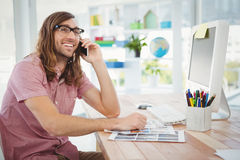 Happy hipster using mobile phone at computer desk Stock Images