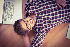 Happy hipster wearing eye glasses lying on hardwood floor Royalty Free Stock Photography