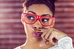 Happy hipster wearing a fake mustache Royalty Free Stock Photo