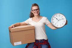 Happy hipster with cardboard box showing clock on blue Stock Photography