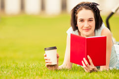 Happy hipster woman in closeup smiling and reading a book. Happy hipster woman in closeup lying on grass, smiling and reading a book while holding a cup of Stock Photography