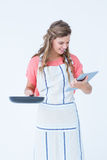 Happy hipster woman holding laptop and frying pan Stock Photo