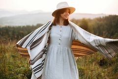Happy hipster woman in poncho and hat enjoying traveling in evening mountains. Stylish boho girl walking in sunny light at royalty free stock image