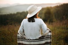 Happy hipster woman in poncho and hat enjoying traveling in evening mountains. Stylish boho girl walking in sunny light at stock images
