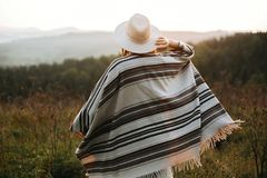Happy hipster woman in poncho and hat enjoying traveling in evening mountains. Stylish boho girl walking in sunny light at royalty free stock photo