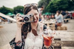 happy hipster woman in sunglasses making photo with old camera a stock photos
