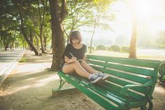 Happy hipster young asian woman writing into her diary in park. Happy hipster young asian woman working on notebook in park. Stock Photos