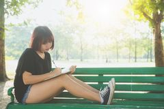 Happy hipster young asian woman writing into her diary in park. Stock Photo