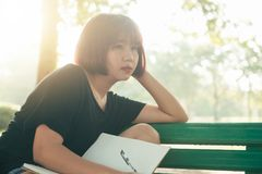 Happy hipster young asian woman writing into her diary in park. Happy hipster young asian woman working on notebook in park. Royalty Free Stock Photography