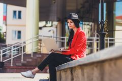Happy hipster young woman working on laptop outdors. Student girl using laptop in university campus. Toned image. Happy hipster young woman working on laptop in Stock Images