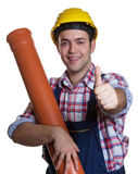 Happy hispanic construction worker with water pipe showing thumb Royalty Free Stock Photo