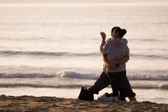 Happy hispanic couple on beach. Couple hugging and looking at a camera Stock Photography