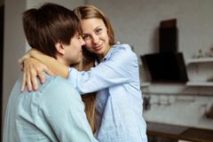 Happy hispanic couple in blue denim cloth embracing in kitchen royalty free stock photo