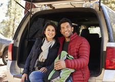Happy Hispanic couple sitting in open back of car before hike royalty free stock image