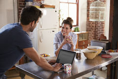 Happy Hispanic couple using computer in kitchen, waist up Royalty Free Stock Images