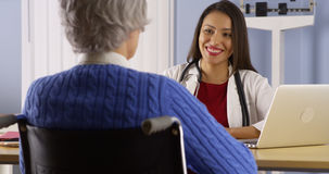Happy Hispanic doctor talking with senior patient royalty free stock photography