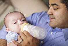 Happy Hispanic Father Bottle Feading His Son Royalty Free Stock Photography