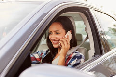 Happy Hispanic female driver using phone in a car Stock Images