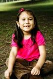 Happy hispanic girl sitting on the grass. Royalty Free Stock Photography