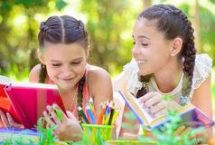 Happy hispanic girls drawing and studying in park Stock Image