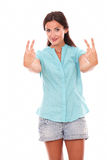Happy hispanic lady making a victory sign Stock Images