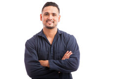 Happy Hispanic mechanic. Young Hispanic mechanic wearing overalls and smiling with his arms crossed Stock Photos