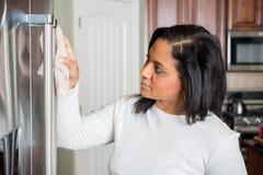 Hispanic Mom Cleaning. Happy hispanic mom cleaning her new refrigerator stock photos