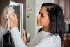 Hispanic Mom Cleaning. Happy hispanic mom cleaning her new refrigerator royalty free stock images