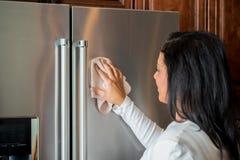 Hispanic Mom Cleaning. Happy hispanic mom cleaning her new refrigerator stock image